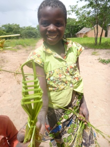 Mika shows off a tiny chair she made by weaving grass.
