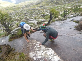 Ba Dennis helps Samuel up slippery rock on the way up Sapitwa.