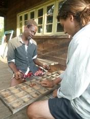 Ba Dennis teaching Samuel how to play Mancala.