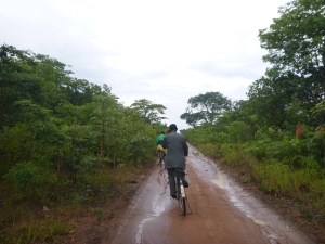 Ba Bernardi talks on his cell phone as we bike, post-rain-storm, to the tarmac road to catch transport to get goats.