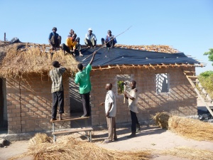 Putting plastic and grass thatch over the Mfuba Community School roof.